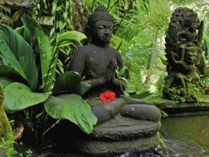 Buddha figure in front of green plants, Ubud, Bali, Indonesia, Asia